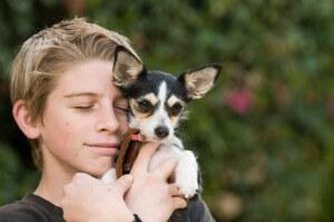 Hund auf dem Arm bei glücklichen Jungen